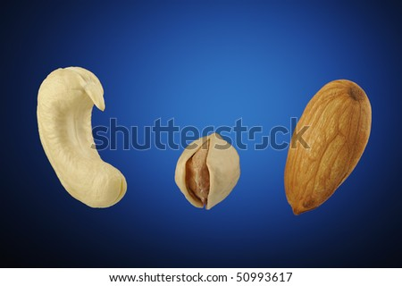 Studio shot of Cashew, pistachio and almond on a blue background