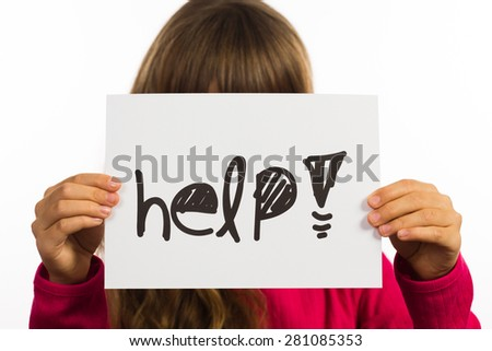 Studio shot of child holding a Help sign made of white paper with handwriting.