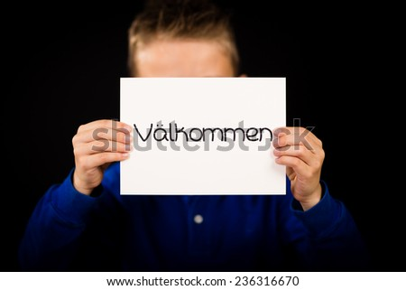 Studio shot of child holding a sign with Swedish word Valkommen - Welcome