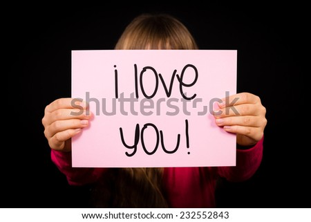 Studio shot of child holding an I Love You sign made of white paper with handwriting.
