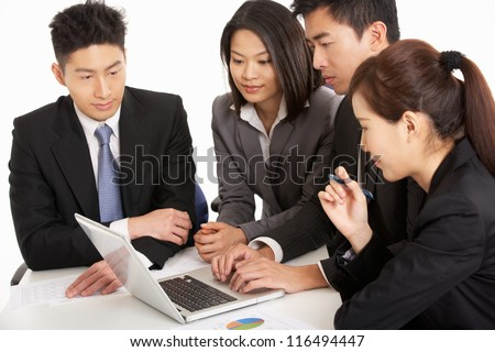 Studio Shot Of Chinese Businesspeople Having Meeting