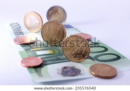 studio shot of complete set of euro coins on 100 euro bank note. symbol for european economy, business, banking and finance - stock photo