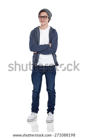 Studio shot of confident little boy wearing glasses and cap standing with his arms crossed  looking away smiling on white background - stock photo