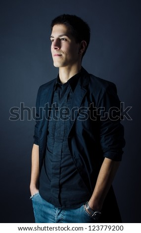 Studio shot of confident young man on dark background