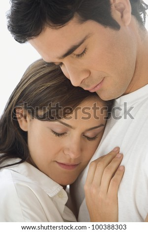 Studio shot of couple hugging with eyes closed