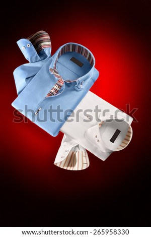 Studio shot of couple of man's shirts with ties on a red background - stock photo