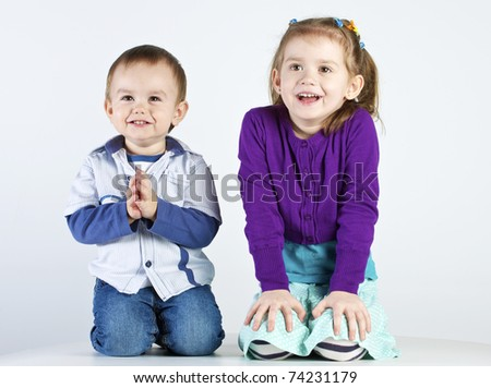studio shot of embracing brother and sister - stock photo
