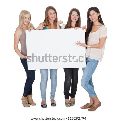 Studio shot of four attractive girls with a blank white board isolated on white - stock photo