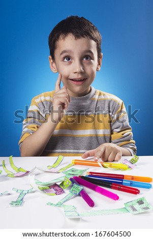 Studio shot of four years old kid who have inspiration for his new drawing. - stock photo