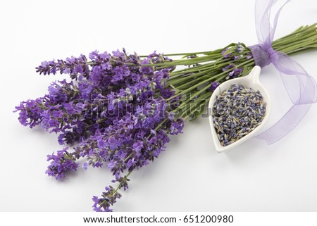 Studio shot of fresh lavender flower bouquet with a purple ribbon, over white background.