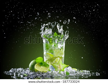 Studio shot of fresh mojito drink with ice cubes and splash on black background - stock photo