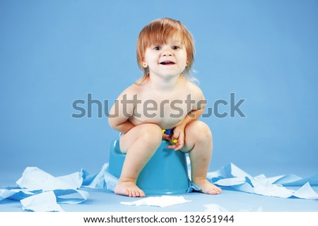 Studio shot of funny toddler sitting on potty chair - stock photo