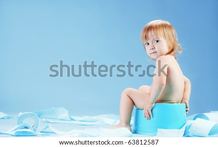 Studio shot of funny toddler sitting on potty chair and playing with toilet paper - stock photo