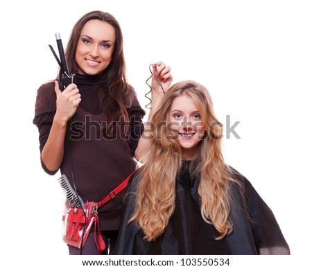 studio shot of hairdresser doing curly hair. isolated on white background - stock photo
