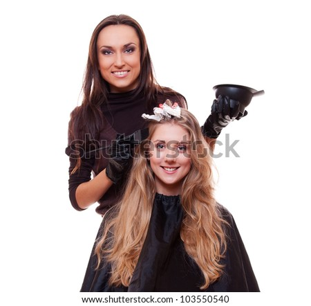 studio shot of hairdresser dyeing woman's hair. isolated on white - stock photo