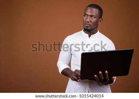 Studio shot of handsome African businessman wearing white shirt against brown background