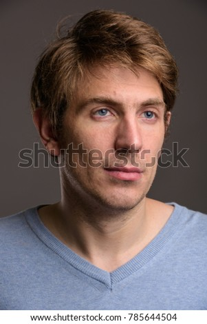 Studio shot of handsome man wearing blue shirt against gray background
