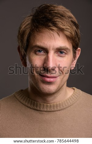 Studio shot of handsome man wearing brown shirt against gray background