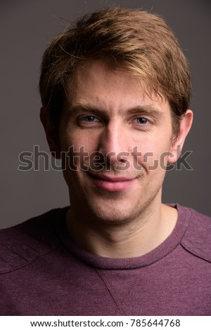Studio shot of handsome man wearing purple long sleeved shirt against gray background