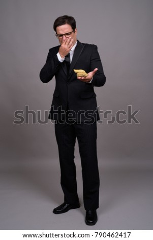 Studio shot of handsome Persian businessman against gray background