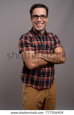Studio shot of handsome Persian man wearing eyeglasses against gray background