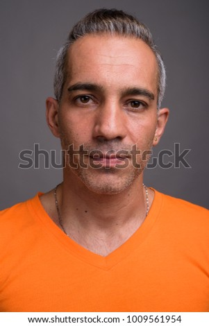 Studio shot of handsome Persian man with gray hair wearing orange shirt against gray background