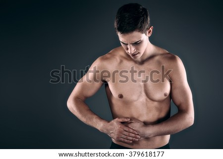 Studio shot of handsome young man with naked torso. Man suffering from abdominal pain