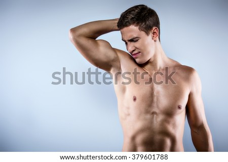 Studio shot of handsome young man with naked torso. Muscular man sniffing armpit and wrinkling face because of smell
