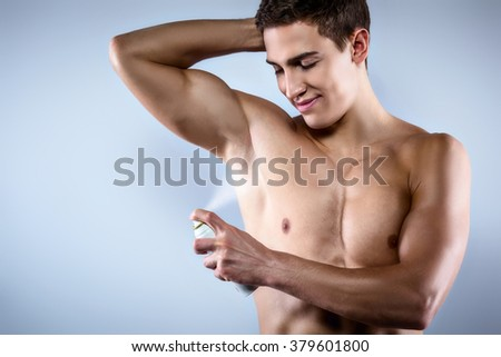 Studio shot of handsome young man with naked torso. Muscular man using deodorant - stock photo