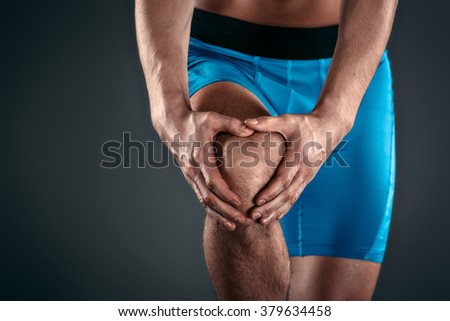 Studio shot of handsome young sportsman with naked torso. Muscular man suffering from pain in knee - stock photo
