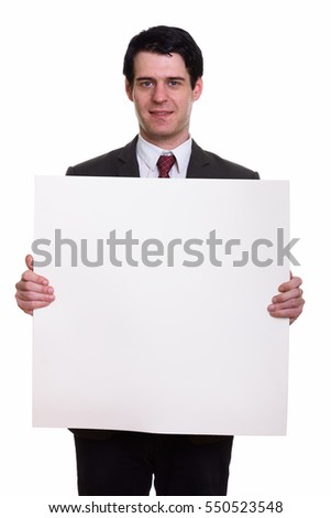 Studio shot of happy businessman smiling and holding copyspace in empty white board isolated against white background