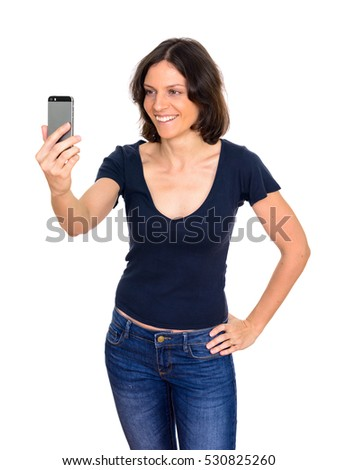 Studio shot of happy Caucasian woman taking selfie with mobile phone while smiling isolated against white background
