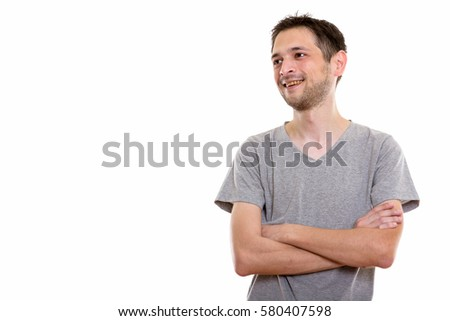 Studio shot of happy young man smiling and thinking with arms crossed