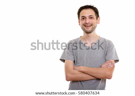 Studio shot of happy young man smiling with arms crossed
