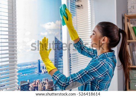 Studio shot of housekeeper. Beautiful woman cleaning jalousie and window at office and smiling