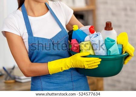 Studio shot of housekeeper while cleaning office. Woman wearing gloves and holding bowl full of bottles with disinfectant