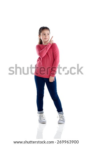 Studio shot of little girl pointing at copyspace on white background - stock photo