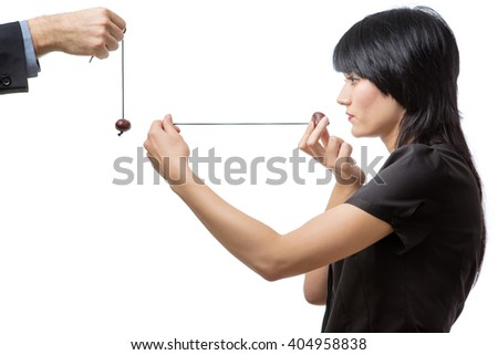 Studio shot of male and female business co-workers having a game of conkers, isolated on white.