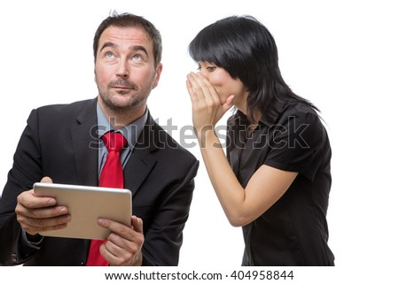 Studio shot of male and female co-workers discussing working she is whispering something into his ear