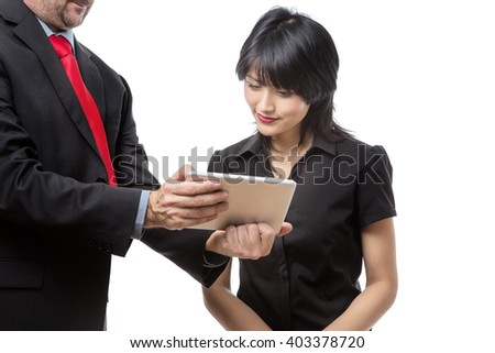 Studio shot of male and female co-workers discussing working together using a tablet computer. Isolated on white