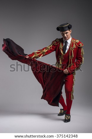 Studio shot of man dressed as Spanish torero, matador, bullfighter. Performing a traditional classic bullfight, standing and holding the capote. - stock photo