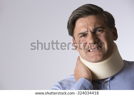 Studio Shot Of Man In Pain Wearing Neck Brace - stock photo