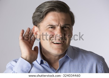 Studio Shot Of Man Suffering From Deafness - stock photo