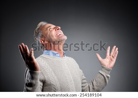 Studio shot of mature man looking up with his arms outstretched over grey background  - stock photo