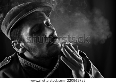 Studio shot of middle aged man who is poisoning himself with cigarette. - stock photo