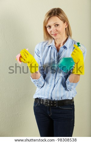 Studio Shot Of Middle Aged Woman Holding Cleaning Products - stock photo