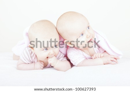 studio-shot of  6 month old identical baby twin sisters lying on bed.