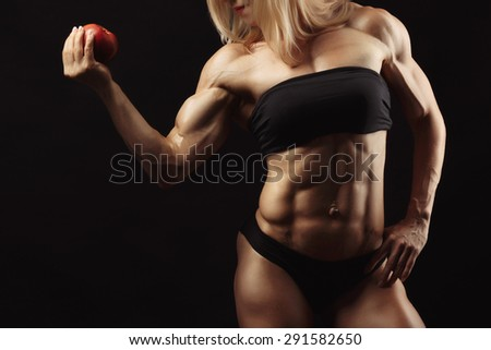 Studio shot of muscular young woman with blond hair in her right hand holding a red apple - stock photo