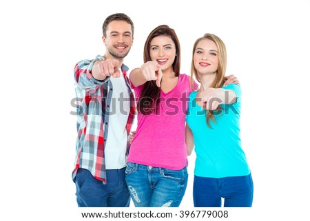 Studio shot of nice young friends. Beautiful people looking at camera, pointing at camera and smiling. Isolated background - stock photo