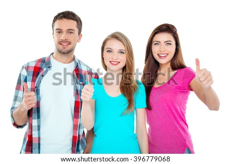 Studio shot of nice young friends. Beautiful people looking at camera, showing thumbs up and smiling. Isolated background - stock photo